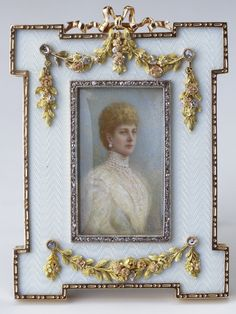 Fabergé rectangular strut frame with projecting corners and a wide border of oyster wave guilloché enamel, mounted in gold with four-colour gold floral swags and pierced ribbon crest. The rectangular bezel of rose diamonds is inset with a photograph of Queen Alexandra. Bought by Queen Alexandra; by whom given to Queen Mary for her birthday, 26 May 1911.
