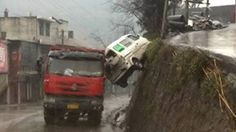 A Chinese motorist had a lucky escape when his mini bus plunged down a sheer drop off a mountainside road – and was 'caught' by a passing lorry.