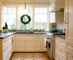 Pretty creamy white kitchen cabinetry & gorgeous vent hood!