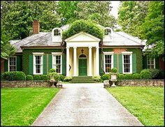 Small scale Classical house.  Tall windows actually originate from Italy, home of the Classical style, of course.  Opened, they allowed more air to flow through the house.  Flemish bond brick in 2 colors creates pattern where it peeks out from the ivy.  The mass of wisteria atop the pediment lends context to the tall dormers.