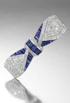 SAPPHIRE AND DIAMOND BROOCH, ca. 1920s  Designed as a bow, pierced and millegrain-set with calibré-cut sapphires and circular-cut diamonds.