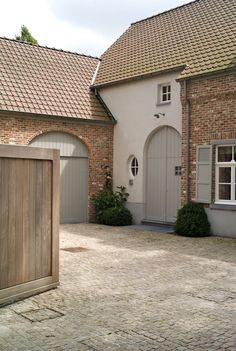 French grey woodwork, soft white render and red brick