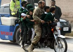 Pakistani soldier rescues children on a motorbike near the site of the attack,16.12.14