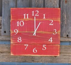 """This pallet style clock has been painted barn red, and then weathered around the edges for a rustic look. White numbers and hands give it a """"red barn"""" feel. * Clock measures approx. 14"""" by 14"""" *Comes"""