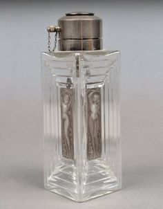 Lalique Isadora Duncan Perfume Atomizer. Clear glass square bottle, the sides with grey tinted glass figural panel, metal atomizer mechanism, etched R. Lalique signature and France on the bottom.