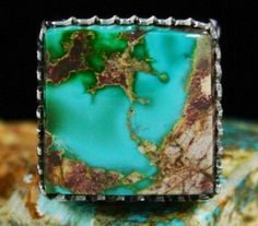 Leonard Nez Rare Gem Grade Royston Turquoise Ring #LeonardNez Leonard Nez has set a fabulous large two toned gem grade natural Royston turquoise cabochon in this fine ring. The gem combines dazzling hues of sky blue flowing into deep green with gold and chocolate host rock matrix. It sits in a hand cut bezel on an extra heavy ten gauge shank. The band of the piece is deeply stamped with lines that radiate out from the underside of the ring face. Leonard has hand etched two large portions of…