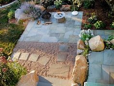 A creative approach to a patio design, the paver path leads to two stone patios in this beautiful garden. Lined with large rocks and colorful plants, this patio area creates a lovely spot for enjoying a fire in the small portable fire pit.
