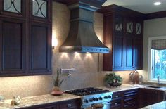Kitchen. Marvelous Range Hood Designs For Beauteous Kitchens Ideas. Terrific Hood Designs Kitchens Decoration With Dark Chimney Range Hood On Mounted Wall Ceramic Tiles Combined Classic Wooden Cabinet And Slick Granite Counter Top Also Nice Stove Ideas. Many ways to make your kitchen more comfortable and healthy. Addition of furniture in the kitchen depends on the funds that we have. Chimney range hood may be an additional option of your kitchen to provide comfort and luxury in it.