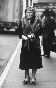 Woman wearing a mink stole and bow shoes, a photo by Diane Arbus, New York City, 1956