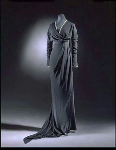"This striking asymmetrical dinner dress was made by Lucile between 1910 and 1912. It was designed for a woman in ""half-mourning"", the third phase of the very complicated Victorian mourning practices which still lingered in the Edwardian era. Half-mourning allowed for the addition of white, gray and lavender to black mourning garments and also allowed for additional jewelry and ornamentation."