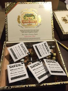 Tuxedo shot glasses tied to a bottle of liquor with tulle tagged groomsman, handed out in cigar box