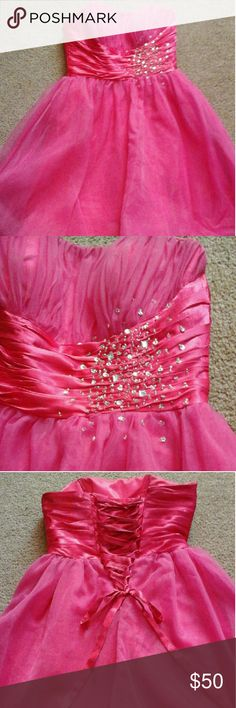 Hot pink short prom dress Hot pink, knee length, strapless dress with corset back. It's got built in/structured bust. Pretty sash with gems. Fits anywhere from a six to a ten, because of the corset back. It works best for someone with a bigger bust. There's a modesty panel behind the lacing, that could be folded back if wanted. Worn twice, and there's signs of someone having a spray tan on the inside, but it's pretty minor, and doesn't show from the outside. No brand Dresses Prom