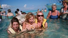 Say cheese! These three women had just been snorkeling in the Cayman Islands when this stingray leapt on their backs during a photo op