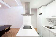 cuisine moderne blanche avec mur en brique peint et îlot