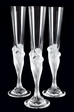 Set of Six Art Deco Style Molded Glass Majestique Champagne Flutes   After Erte, manufactured by Cristallerie de Sevres   Each in frosted and glossy colorless glass, with a stem decorated with seven female heads with long flowing hair and head veils, suggestive of upward billowing clouds of smoke. Height 12 inches.