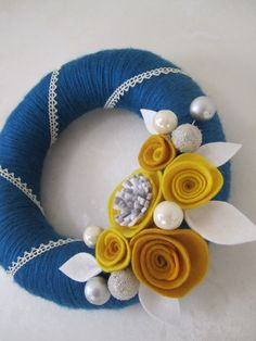 Blue yarn wreath with felt flowers