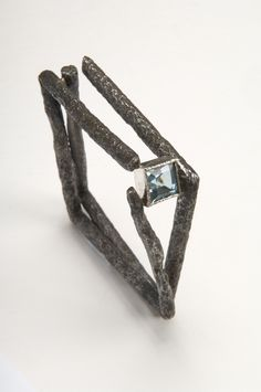 Willem Heyneker - Bracelet constructed from found steel (rusty tent pegs) and a synthetic blue topaz.
