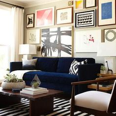 Living Room with Blue Velvet Sofa, Black & White Striped Rug and Grey Wall with Framed Art Gallery | Emily Henderson