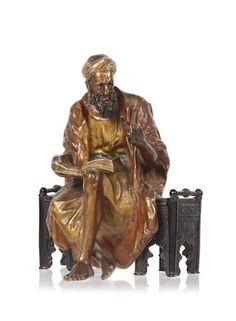 A late 19th/early 20th century Austrian cold painted bronze figure Of a seated Middle-Eastern scholar reading a book.