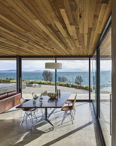 The dining table and chairs are by Charles and Ray Eames. The ceiling, which extends beyond the building's envelope, is made of Tasmanian oak.