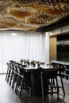 "In the lobby, guests are met with a black-tinted glass box displaying bottles of wine, which the architects describe as ""part object, part installation""."