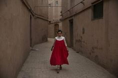 A Uighur woman wearing a gown for the Eid holiday walks from her house on July 2014 in old Kashgar, Xinjiang. Eid Holiday, Silk Road, Old Hollywood, Looks Great, Women Wear, China, How To Wear, Lebanon, Gown