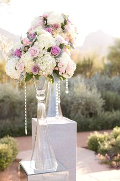 Blush pink and white hydrangeas and roses, crystal tear drops, and tall glass vases sparkle and glow in the golden afternoon sun.