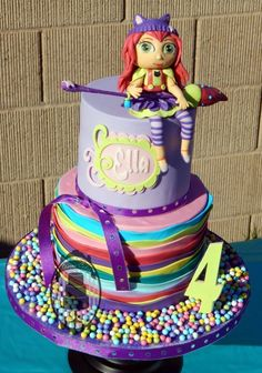 2 tier Little Charmers birthday cake, looks Amazing! love the Hazel fondant figure, the colorful rainbow base layer and candy decorations.