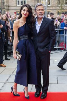 Amal Clooney attends the People's Postcode Lottery Charity Gala in Edinburgh, Scotland with George Clooney in a chic navy one-shoulder jumpsuit. Amal Clooney, Flower Carpet, Hollywood Couples, Hollywood Star, One Shoulder Jumpsuit, Fashion Couple, Red Carpet Fashion, Timeless Fashion, Dapper