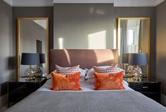 Dark wallpaper creates a luxurious bedroom design. Copper linen fabric headboard with feature bedside lighting. Large mirrors in the alcoves with accent orange velvet cushions. Patterned orange cushions dress the bed perfectly. Glass Bedside Lamps, Bedside Lighting, Orange Cushions, Velvet Cushions, Self Build Houses, Edwardian House, Dark Wallpaper, Contemporary Bedroom