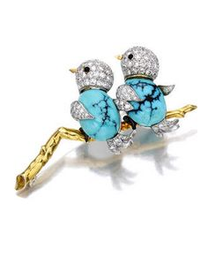 A turquoise, diamond and garnet brooch designed as two pavé-set diamond birds, each set with an oval turquoise cabochon body, enhanced by garnet cabochon eyes and black enamel feet, perched on a polished gold branch; with English hallmarks (indistinct); estimated total diamond weight: 2.10 carats; mounted in eighteen karat gold and platinum; length: 2 1/4in.