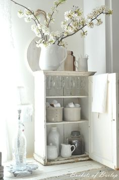 Our farmhouse breakfast room...with a vintage cupboard for housing coffee items. Pear blossoms welcome spring