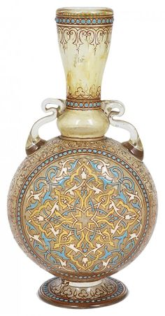 A FRENCH ENAMELLED GLASS MAMLUK STYLE FLASK, PHILIPPE-JOSEPH BROCARD, PARIS, CIRCA 1880 flattened moon form, the amber tinted glass body enamelled in turquoise, white and red and gilded with arabesque strapwork roundels to each side within beaded borders, gilt scroll work between and to the flared neck, scroll handles applied to the shoulder, signed Brocard Paris in iron red script above the foot 16.5cm high Judy Rudoe (Decorative Arts 1850-1950.