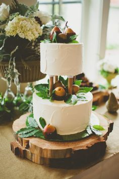 caramel and chocolate dipped pears and greenery on top of a two tiered white wedding cake -- autumn wedding inspiration