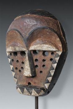 Pende maske kindombolo - Der Maskentyp kindombolo stellt einen furchteinflössenden Charakter unter den Mbuya-Masken dar: Interpretiert wird dieser Maskentyp, der in Abwandelungen auch als tundu oder munyangi benannt wird, als überheblicher, Schabernack treibender Charakter. Die Bohrungen deuten alte Pockennarben an, da die verkörperte Figur diese schwere Krankheit überlebt hat, gilt diese nun als unverletzlich und tritt entsprechend überheblich und arrogant auf. ca. 23 x 16 x 8: ca. 380 gr.