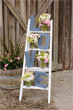 Place letters on a ladder with flower arrangements