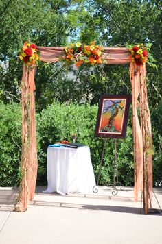 Ceremony arch covered with florals, organza fabric & curly willow branches