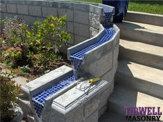 concrete wall with channel on top to direct flow of water from downspout to the alley