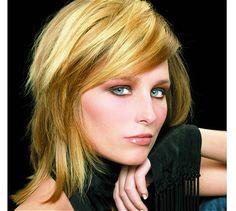 Les cheveux de cette jeune femme sont coupés en carré dégradé, à mi-longueur. La coloration blonde est accentuée de mèches plus foncées, en dégradé de tons châtains, ce qui apporte des reflets à la chevelure, lui donnant plus de volume. Cette couleur fait particulièrement ressortir le teint clair de cette femme.