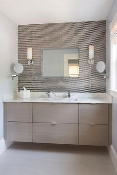 Contemporary bathroom features a taupe veneer floating vanity topped with white…