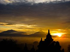 sunrise at the Borobudur Temple, Magelang, Central Java, Indonesia. The two mountains in the background are Mount Merbabu and Mount Merapi