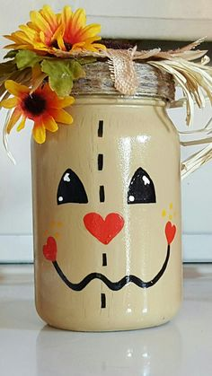 Mason Jar Scarecrow! Jar spray painted white let dry overnight,arcylic craft paint in kahki,harvest orange,black,white let dry,clear gloss fast dry spray let dry, glue gun twine to lid cover, glue straw and fake flower. So cute for fall! Spray Paint Mason Jars, Painted Mason Jars, Painted Bottles, Fall Mason Jars, Mason Jar Lids, Mason Jar Crafts, Fall Craft Fairs, Fall Crafts, Bottles And Jars