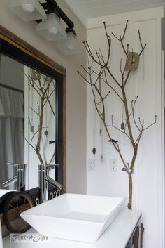 branch jewelry holder in bathroom / Salvaged farmhouse bathroom makeover via http://www.funkyjunkinteriors.net/