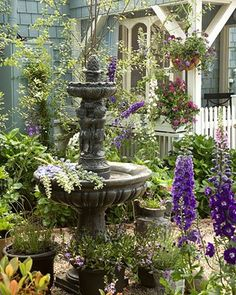 Cottage garden with fountain and hanging plants.