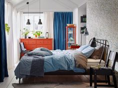 A medium sized bedroom with a dark grey steel bed for two, with bedlinen in light blue and grey. Shown together with a red chest of drawers with four small drawers and four large drawers.