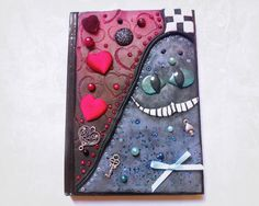 Half Queen of Hearts themed and half Alice themed notebook Made using Polymer Clay, beads, Mica Powders and charms. You can buy this herr https://www.etsy.com/uk/listing/154169275/alice-in-wonderland-inspired-notebook?ref=pr_shop #aliceinwonderland #polymerclay #cheshirecat #redqueen #queenofhearts #charms #journal