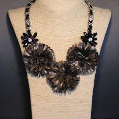 Collar de bisutería con cadena color plata i tira de tela color negro intercalada, tiene 3 flores en tela y dos flores realizadas en canutillos de cerámica y cristal.