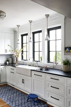 Farmhouse Style Kitchen in White and Black with accents of blue in the rug runner and kitchen stool #kitchen
