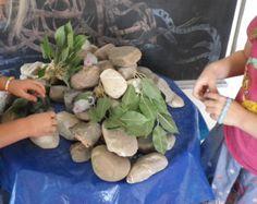 """Thema:"""" Max en de Toverstenen"""" (zie prentenboek) Bouwen met grote stenen: """"Maaskeien"""" (van de tuinhandel.) Stapel de stenen op elkaar en maak de grote rots van de rotsmuizen    Een rots met holletjes voor de rotsmuizen, verstop er kleine speelmuizen (dierenhandel) in en glazen steentjes.(aquariummateriaal)"""