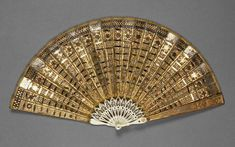 Folding fan of ivory sticks, pierced and set with silver spangles. Double leaf of cream net backed by gauze, decorated with frosted gilt-metal paillettes (pierced panels) overlaid by cut steel spangles of graduated size. Guards overlaid from the shoulder by gilt metal panels decorated with frosted gilt metal paillettes. Possibly Scottish c1800. Fitzwilliam Museum